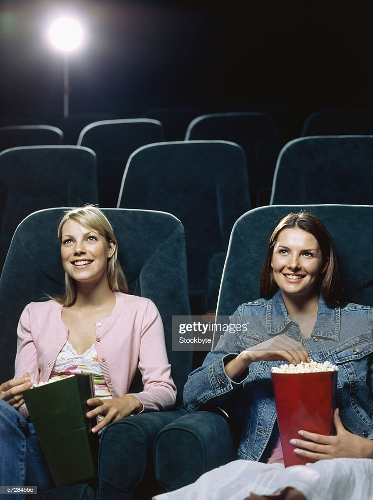 Two young women watching movie in a movie theatre : Stock-Foto