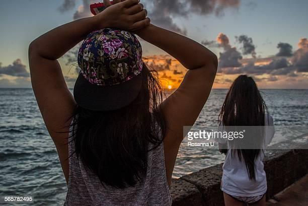 Two young women watching sunrise, Kaaawa beach, Oahu, Hawaii, USA