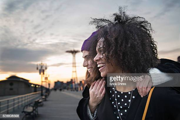 two young women watching sunset from boardwalk - adults only photos stock pictures, royalty-free photos & images