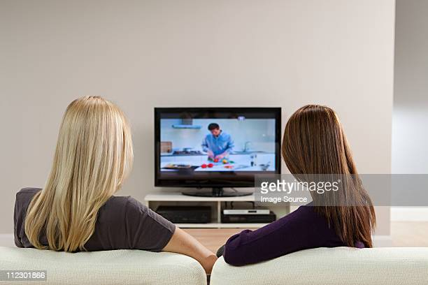 Two young women watching television