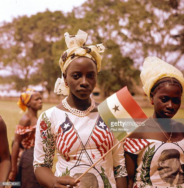 Two young women wear dresses depicting the Liberian flag and political leaders during the country's national commemoration day