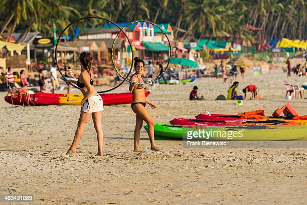 Two young women wearing bikinis are playing with a hoop at Palolem Beach with blue sky palm trees and white sand