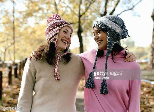 Two young women wearing bobble hats, arms around one another, smiling