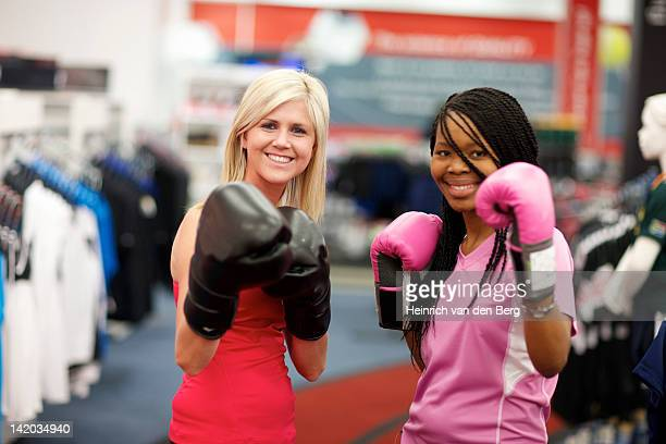 Two young women wearing boxing gloves and looking at the camera, Pietermaritzburg, KwaZulu-Natal, South Africa