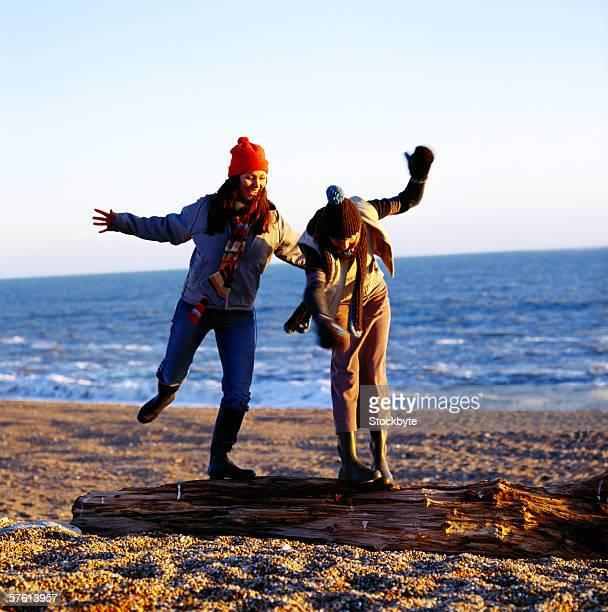 Two young women wearing caps having fun at the beach
