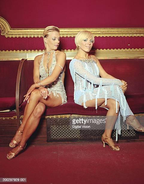 Two young women wearing dancing costumes, sitting on sofa