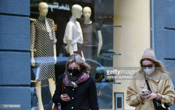 Two young women wearing face masks amid concerns of the COVID19 coronavirus walk past the shop window of a fashion boutique on a warm spring day in...