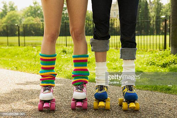 Two young women wearing roller skates, low section