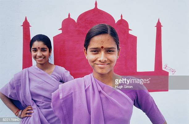 two young women wearing sari and standing in front of mural painting of taj mahal - hugh sitton stock pictures, royalty-free photos & images