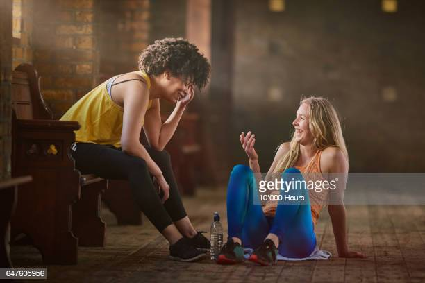 two young women wearing sports clothing talking in gym. - dansstudio stock pictures, royalty-free photos & images