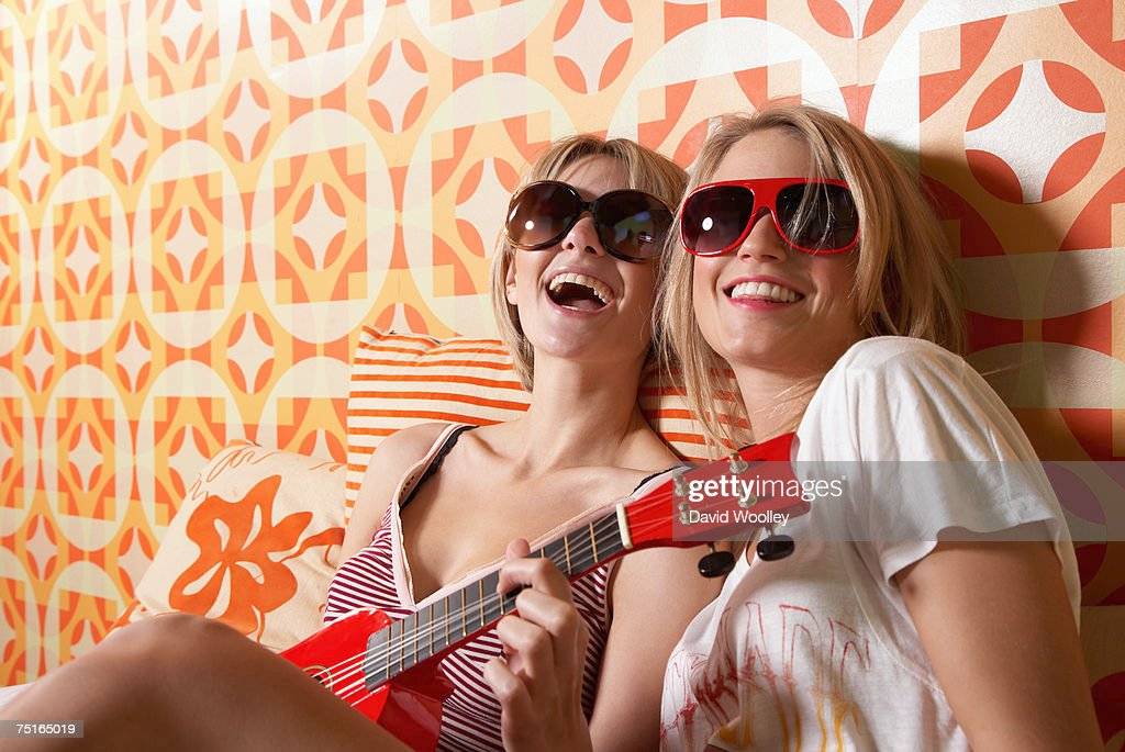 Two young women wearing sunglasses, sitting on bed, one playing guitar, laughing : Stock Photo