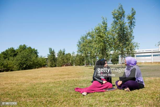 Two young women wearing the hijab sitting in a park.
