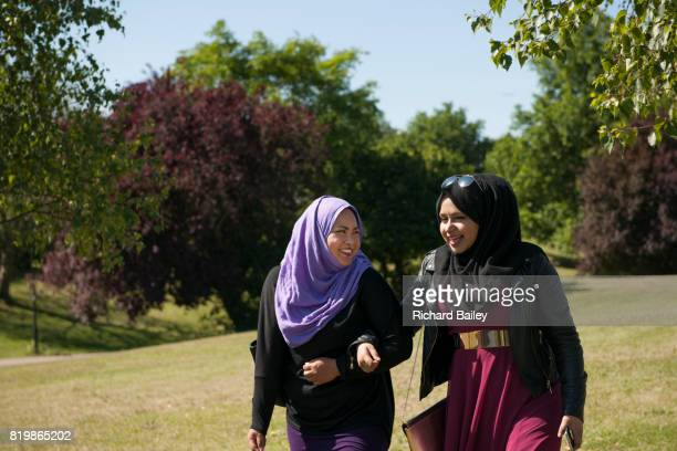 Two young women wearing the hijab walking in a park