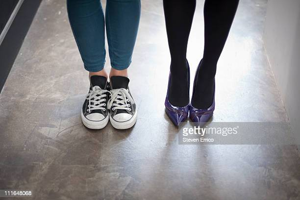 Two young women wearing very different shoes