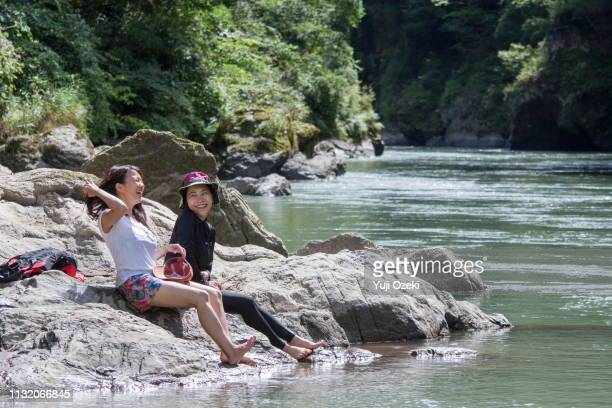 Two young women who are relaxing on the river rock