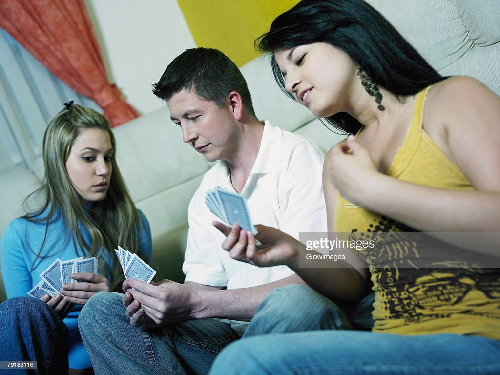 Two young women with a mid adult man playing cards : Stock Photo