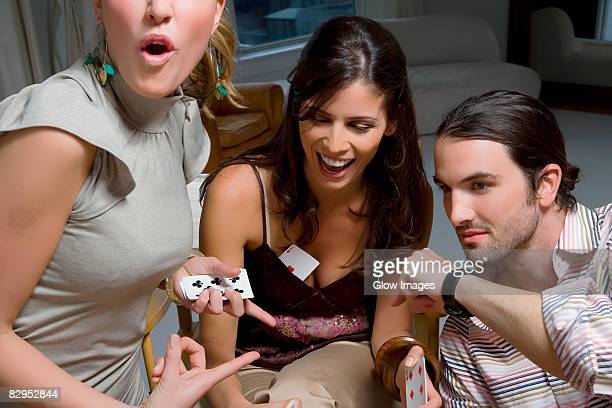 two young women with a young man playing cards - man met een groep vrouwen stockfoto's en -beelden