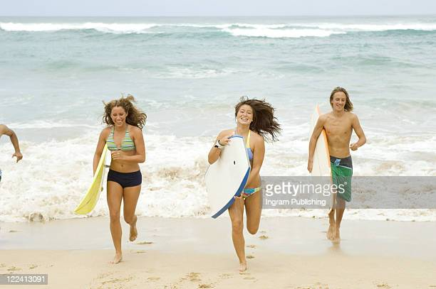 Two young women with a young man running on the beach