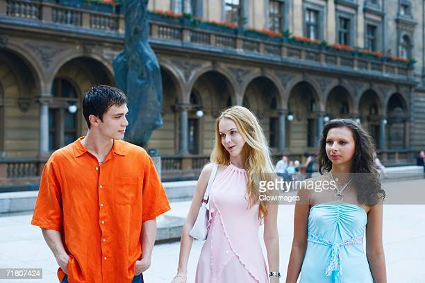 Two young women with a young man walking side by side