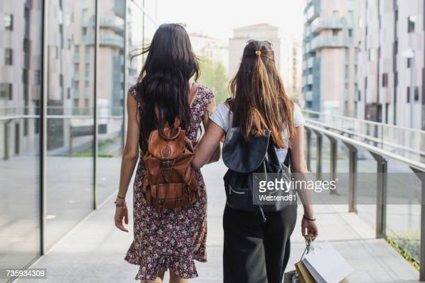 Two young women with backpacks and shopping bags walking in the city