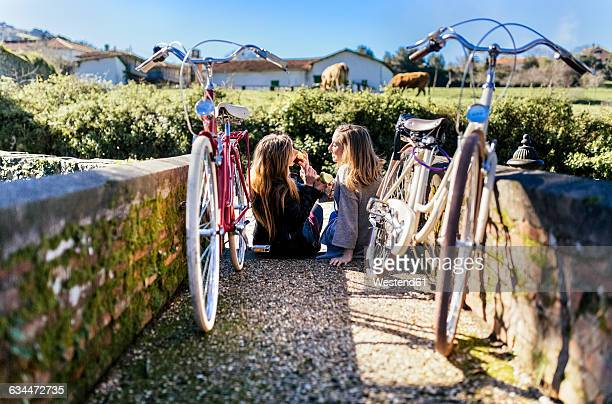 Two young women with bicycles eating apples outside
