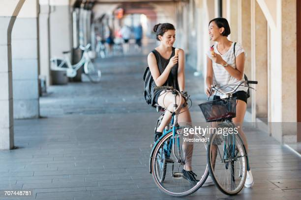Two young women with bicycles eating icecream