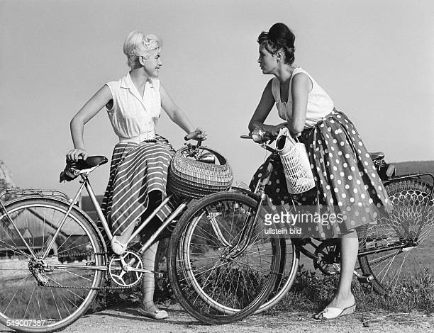 Two young women with bicycles in a talk lete fifties