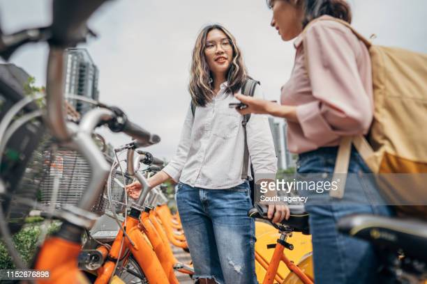 two young women with bicycles - bicycle parking station stock photos and pictures