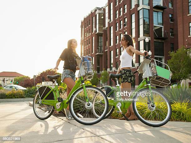 Two young women with bike shares in city