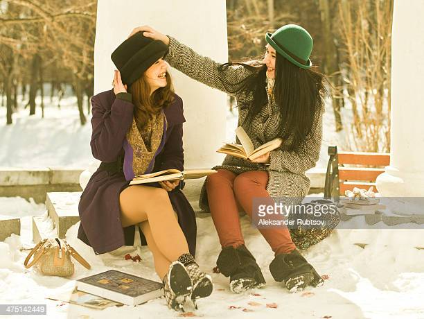Two young women with books on park bench in snow