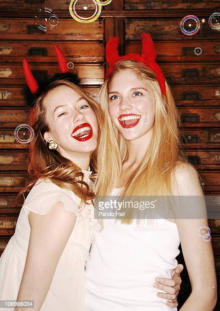 two young women with devil horns laughing - devil costume stockfoto's en -beelden