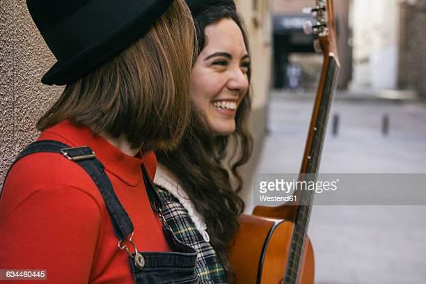 Two young women with guitar having fun