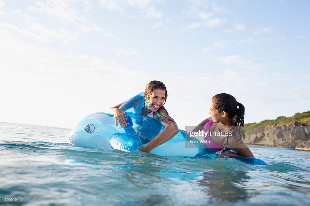 Two young women with inflatable toy in sea : ストックフォト