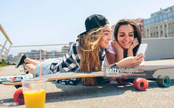 Two young women with longboards enjoying summer