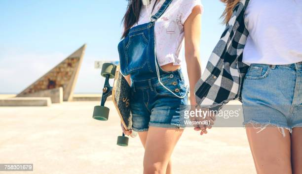Two young women with longboards walking hand in hand on beach promenade, partial view