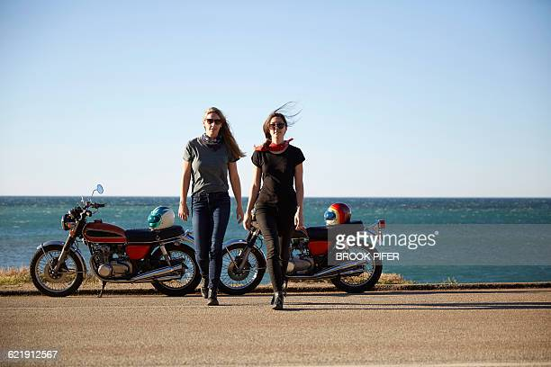 Two young women with motorcycles on empty road