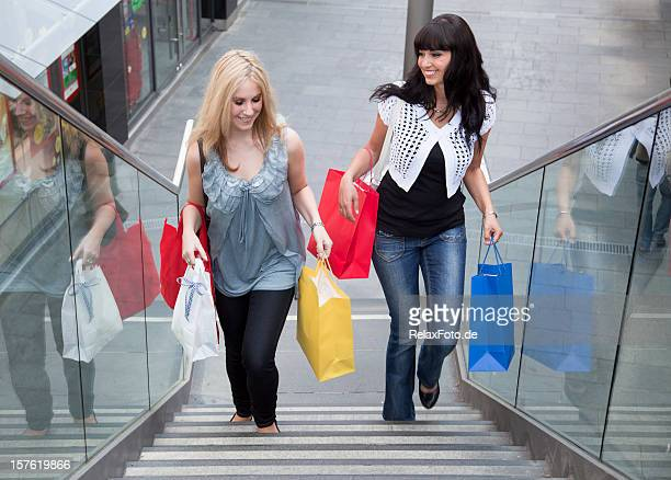 Two young women with multi colored shopping bags on staircase