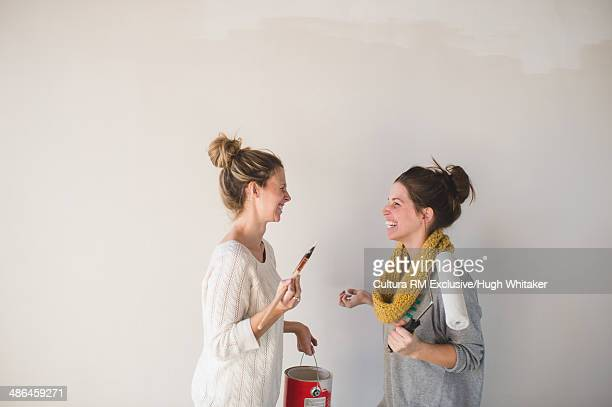Two young women with paintbrushes chatting