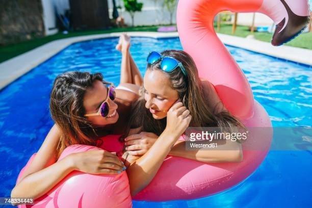 Two young women with pink flamingo float in swimming pool