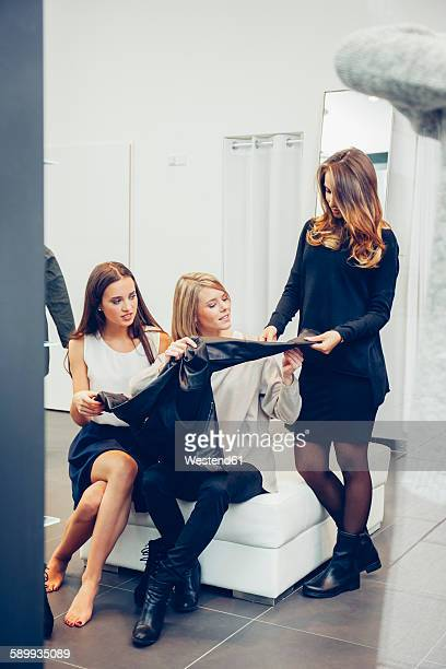 Two young women with shop assistant in a boutique