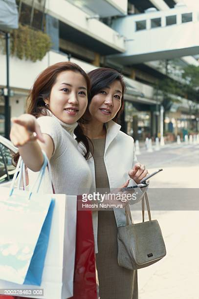 Two young women with shopping bags outdoors, woman pointing