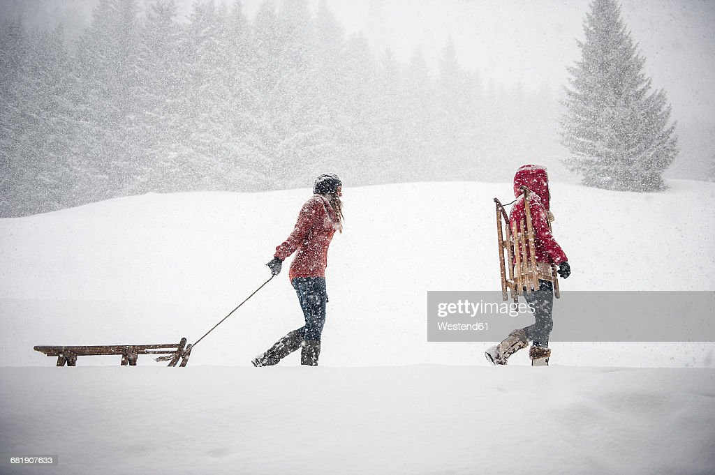 Two young women with sledges in heavy snowfall : Stock Photo