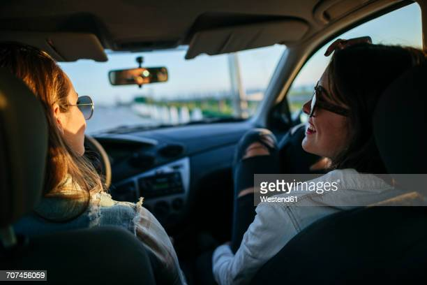 Two young women with sunglasses relaxing in car at evening twilight