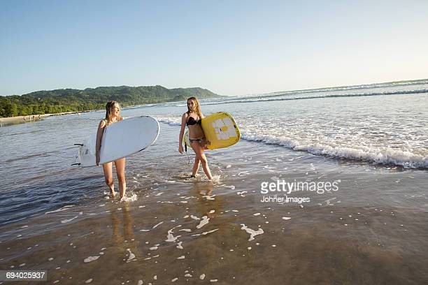 Two young women with surfboards wading in water