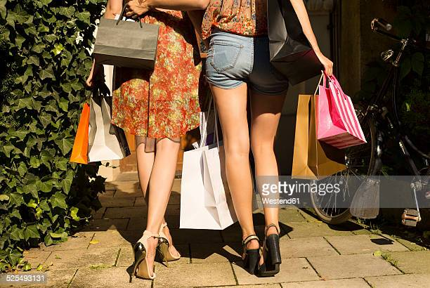 two young women with their purchases, partial view - hoge hakken stockfoto's en -beelden