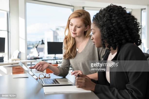 Two young women working in office with laptop