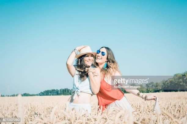 Zwei junge Frauen, Freundinnen im Weizenfeld Spaß