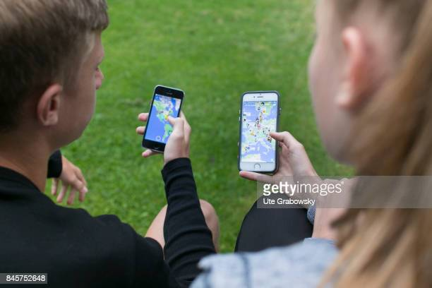 Two youngsters are looking at maps on which friends are marked on Snapchat a social media app on a smartphone Staged picture on August 10 2017 in...