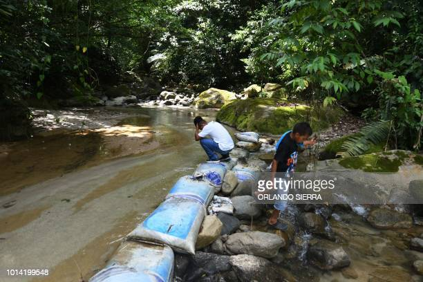 Two youngsters remain at the basin of the Mezapa river which rises in the Nombre de Dios mountain range where the Centrales El Progreso hydroelectric...