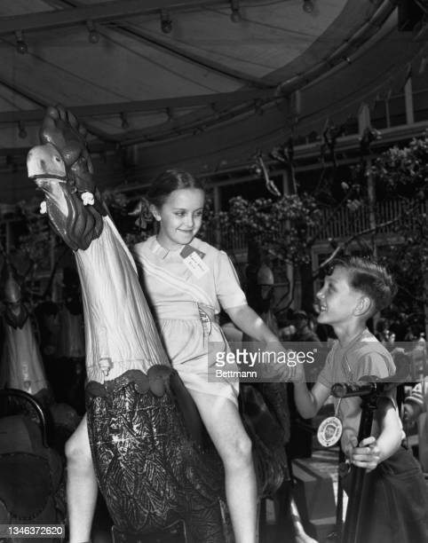 Two youngsters, Renold Stephens of Britain and Eugenia Safonov of Russia, both children of United Nations officials, on a Merry-Go-Round at the...